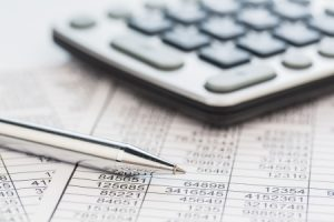 18597956 - a calculator is on a balance sheet numbers are statistics  photo icon for sales, profit and cost